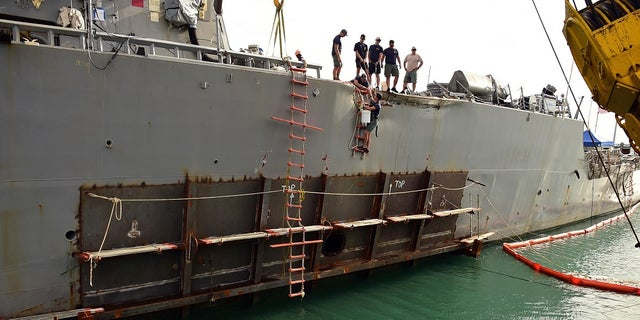 In this October 5, 2017 photo, a temporary patch is welded to the area damaged by a collision aboard USS John S. McCain.