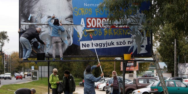 Activists remove a government billboard displaying George Soros in monochrome next to a message urging Hungarians to take part in a national consultation about what it calls a plan by the Hungarian-born financier to settle a million migrants in Europe per year.