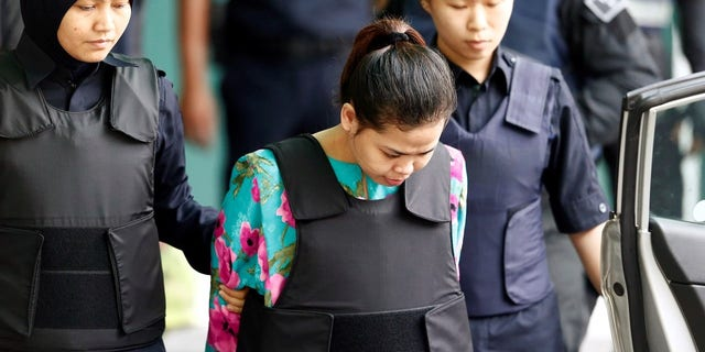 Indonesian Siti Aisyah, who is on trial for the killing of Kim Jong Nam, is escorted into Kuala Lumpar airport.