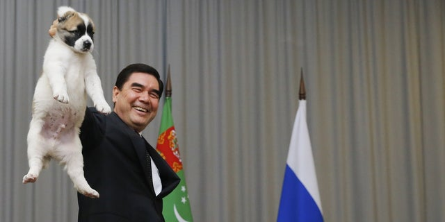 Turkmenistan's President Gurbanguly Berdimuhamedov holds up a Turkmen shepherd dog.