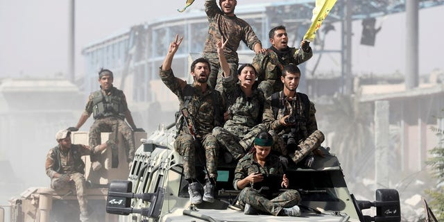 Syrian Democratic Forces (SDF) fighters ride atop military vehicles as they celebrate victory in Raqqa against ISIS soldiers.