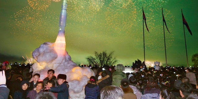 North Koreans pose in front of ICBM Hwasong-15 ice sculpture during New Year's Day celebration