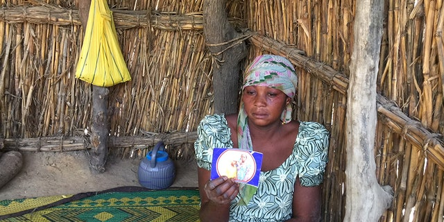 The mother of one of the abducted girls holds up a photo.