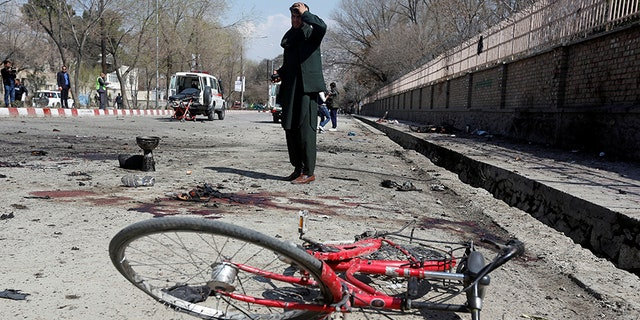 An Afghan man inspects the site of a suicide attack in Kabul.