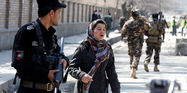 An Afghan woman seeks for her relative at the site of a suicide in Kabul.
