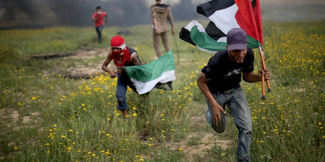 Palestinian demonstrators run during clashes with Israeli troops near the border with Israel, in the southern Gaza Strip March 23, 2018.