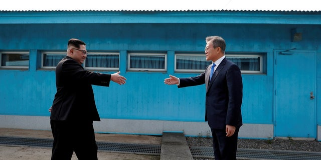 South Korean President Moon Jae-in and North Korean leader Kim Jong Un (L) are about to shake hands on their first ever meeting at the truce village of Panmunjom inside the demilitarized zone separating the two Koreas.