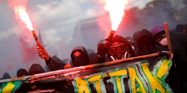 Masked protesters hold safety flares during the traditional May Day labor union march in Paris, France.