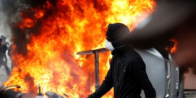 A masked protester walks near a car that burns outside a Renault automobile garage during clashes during the May Day labor union march in Paris, France.