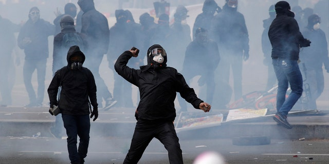 Tear gas fills the air as a masked protester throws a rock during clashes at the May Day labor union rally in Paris, France.