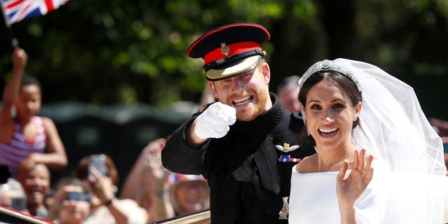 "Meghan Markle and Prince Harry during the carriage procession after saying ""I do."""