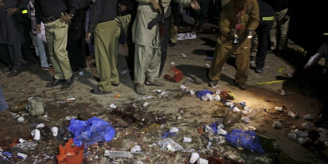 Security officials gather at the site of a blast in Lahore, Pakistan.