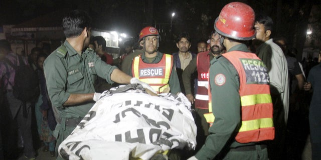 Rescue workers move a body from the site of a blast in Pakistan.