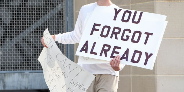 A fan stands outside Beaver Stadium protesting the commemoration.