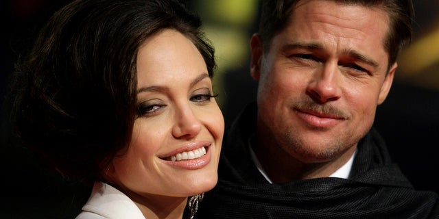 """U.S. actors Brad Pitt and his partner Angelina Jolie pose for photographers on the red carpet at the German premiere of the movie """"The Curious Case of Benjamin Button"""" in Berlin January 19, 2009. REUTERS/Hannibal Hanschke/File Photo     TPX IMAGES OF THE DAY      - RTSOLP8"""