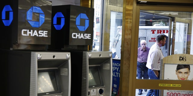 JPMorgan Chase ATMs stand near a door as customers walk past a Duane Reade store in New York, U.S., October 3, 2016. (REUTERS/Lucas Jackson)