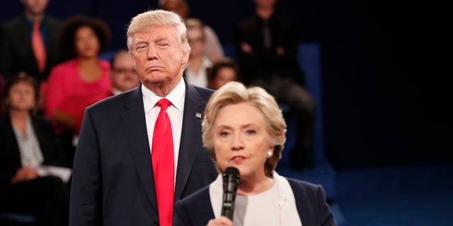 Republican U.S. presidential nominee Donald Trump listens as Democratic nominee Hillary Clinton answers a question from the audience during their presidential town hall debate at Washington University in St. Louis, Missouri, U.S., October 9, 2016. REUTERS/Rick Wilking - HT1ECAA055M6E