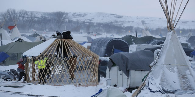 Activists build a shelter near Cannon Ball, N.D., on Monday.
