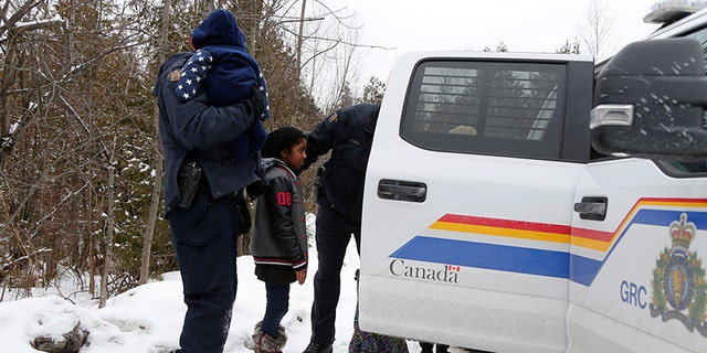 The children of a woman who told police that she and her family were from Sudan are placed in a vehicle as they are all taken into custody by Royal Canadian Mounted Police officers.