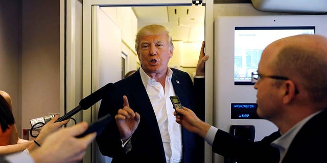 """U.S. President Donald Trump speaks with reporters aboard Air Force One on his way to a """"Make America Great Again"""" rally at Orlando Melbourne International Airport in Melbourne, Florida, U.S. February 18, 2017."""
