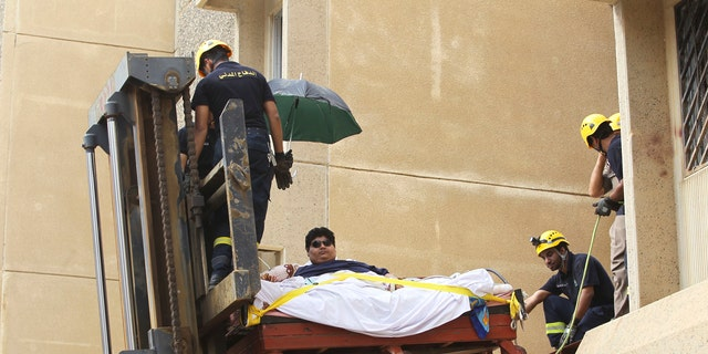 Saudi civil defense members use a forklift to move Khaled Mohsen Shaeri from his house to be airlifted to the capital Riyadh for medical treatment, August 19, 2013. REUTERS