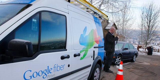 File photo: A technician gets cabling out of his truck to install Google Fiber in a residential home in Provo, Utah, January 2, 2014.