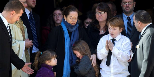 Mimi O'Donnell stands with her children Willa, Tallulah and Cooper at Philip Seymour Hoffman's funeral.