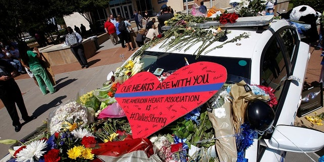 A heart is pictured on a police car that makes up part of a makeshift memorial at Police Headquarters following the multiple police shooting in Dallas, Texas, U.S.,July 8, 2016.  REUTERS/Carlo Allegri - RTX2KEUZ