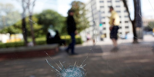 Broken glass from a bullet hole is seen at a bus stop near the shooting scene in Dallas, Texas, U.S., July 8, 2016.  REUTERS/Shannon Stapleton - RTX2KEY1