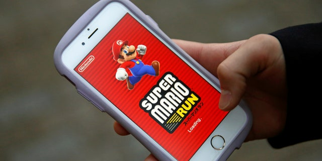 """Takuya Nishya shows Nintendo's """"Super Mario Run"""" game on his smartphone by the request of a photographer in Tokyo, Japan, December 20, 2016. (REUTERS/Kim Kyung-Hoon)"""