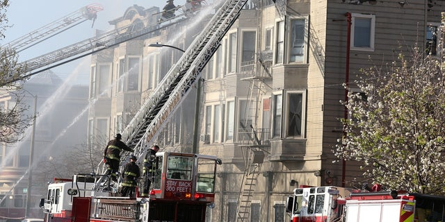 Firefighters battle a four-alarm blaze in a three-story apartment building in Oakland, Calif., March 27, 2017.