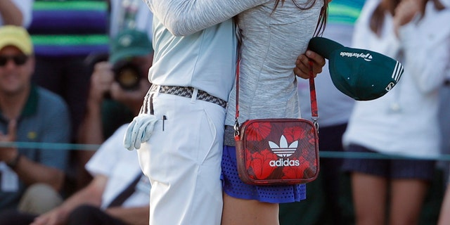 Sergio Garcia of Spain kisses his fiance Angela Akins after he won the 2017 Masters golf tournament.