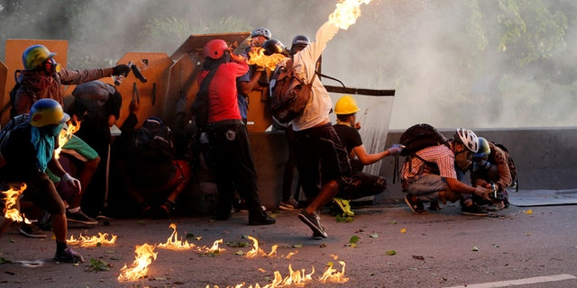 An opposition supporter throws a petrol bomb while clashing with riot security forces during a rally against President Nicolas Maduro in Caracas, Venezuela, May 18, 2017.  REUTERS/Marco Bello - RTX36IDB