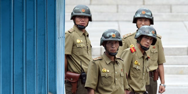 North Korean soldiers watch the south side as the United Nations Command officials visit after a commemorative ceremony for the 64th anniversary of the Korean armistice at the truce village of Panmunjom in the Demilitarized Zone (DMZ) dividing the two Koreas.