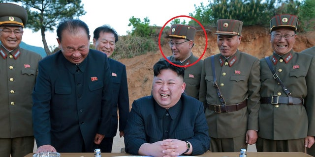 Kim Jong Sik, pictured above, stands with North Korean leader Kim Jong Un as they react during the long-range strategic ballistic rocket test launch.