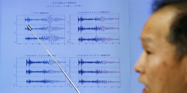 Japan Meteorological Agency's earthquake and tsunami observations division director Toshiyuki Matsumori points at graphs of ground motion waveform data observed in Japan after North Korea's sixth nuclear test.