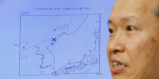 Japan Meteorological Agency's earthquake and tsunami observations division director Toshiyuki Matsumori speaks in front of a screen showing the seismic event that was indicated in North Korea and observed in Japan.