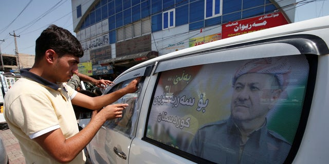 A Kurdish man decorates a car with a poster bearing the image of Iraq's Kurdistan region's President Massoud Barzani, urging people to vote in the September 25th independence referendum, in Erbil, Iraq September 5, 2017.
