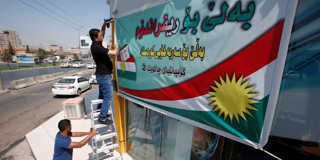 A Kurdish man hangs up a banner, urging people to vote in the September 25th independence referendum, in Erbil, Iraq September 5, 2017.