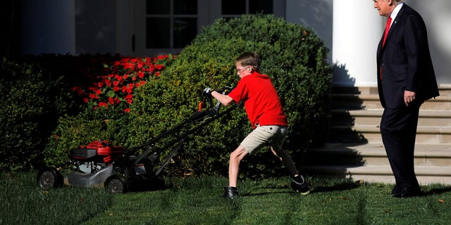 President Trump looks on as 11-year-old Frank Giaccio cuts the Rose Garden grass.