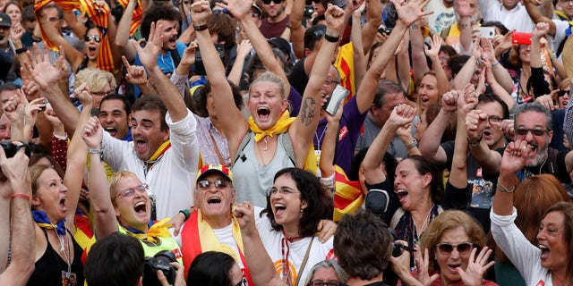 People celebrate after the Catalan regional parliament passes the vote of independence from Spain in Barcelona.