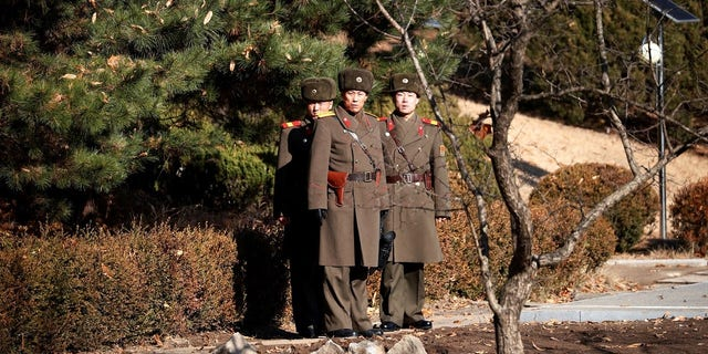 North Korean soldiers looking toward the South at the DMZ. South Korea is reportedly broadcasting news about the defector through loudspeakers.