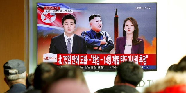 People watch a TV broadcasting a news report on North Korea firing what appeared to be an intercontinental ballistic missile (ICBM) that landed close to Japan, in Seoul, South Korea.