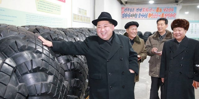 Kim feels the tires that were made to carry the ICBM launched in early December.