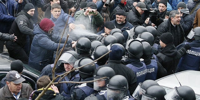 Police officers use tear gas against supporters of Georgian former President Mikheil Saakashvili during clashes.