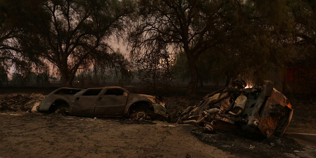 The burned remains of crashed cars are seen at night on a country road as strong winds push the Thomas Fire across thousands of acres near Santa Paula on Tuesday.
