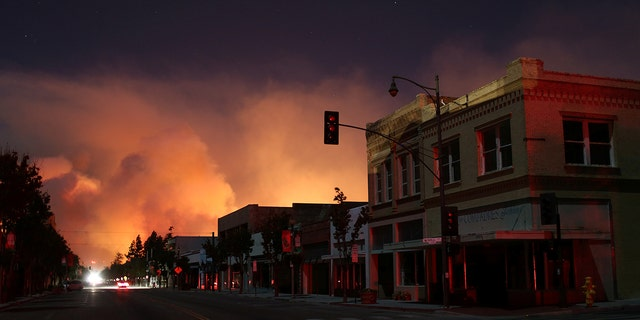 Downtown is darkened by a power outage with smoke rising in the distance in Santa Paula, Calif.