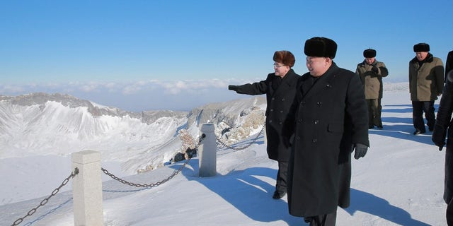 Kim Jong Un strolls the mountain with officials.