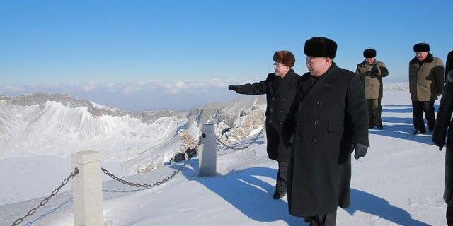 Kim Jong Un strolls the mountain with officials.