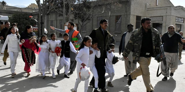 Policemen guide people after gunmen attacked the Bethel Memorial Methodist Church in Quetta, Pakistan.